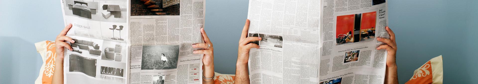 Dwie osoby czytające gazetę